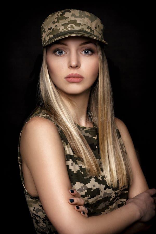 Portret van mooie vrouwenmilitairen in militaire kledij op zwarte achtergrond royalty-vrije stock foto