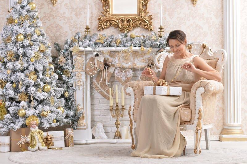 Portret van mooie vrouwenzitting als voorzitter met Kerstmisheden dichtbij boom stock afbeelding