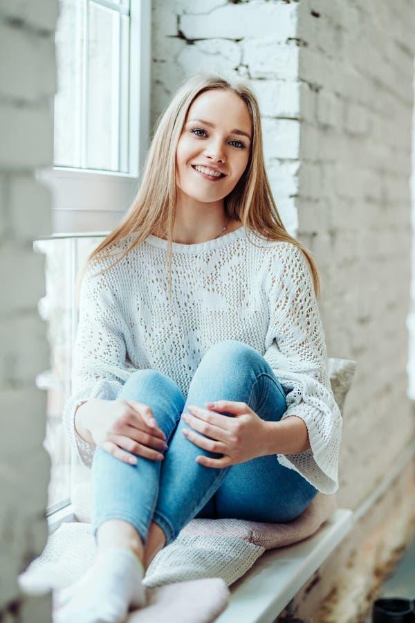 Portret van mooie vrouwenzitting op de venstervensterbank en het glimlachen stock foto's