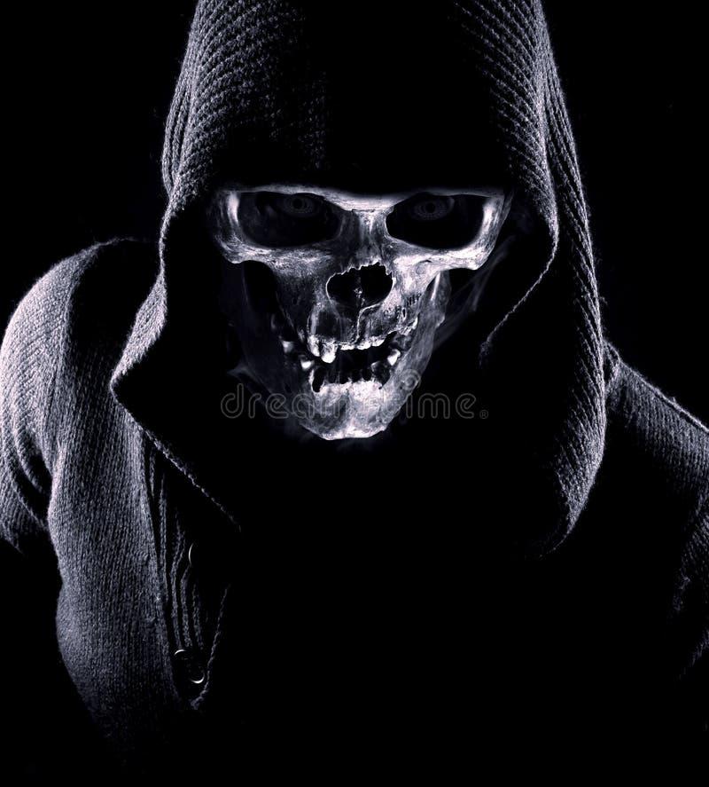 Portret van moordenaar met schedel in plaats van gezicht op de zwarte achtergrond royalty-vrije stock fotografie