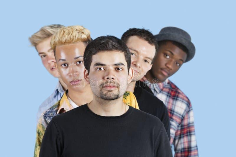 Portret van multi-etnische vrienden die zich in lijn over blauwe achtergrond bevinden stock foto's