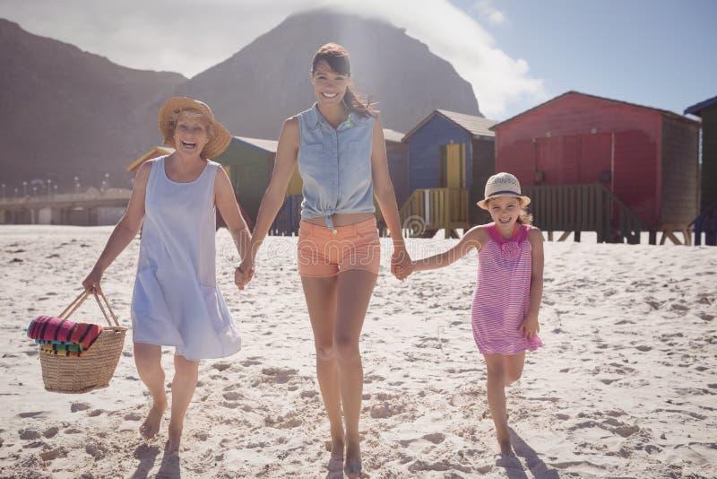 Portret van multi-geproduceerde familie die bij strand lopen royalty-vrije stock afbeeldingen