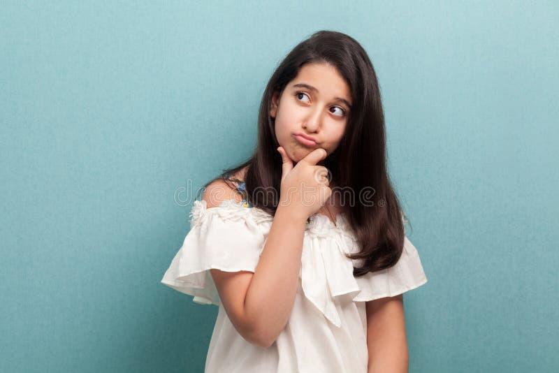 Portret van nadenkend mooi donkerbruin jong meisje met zwart lang recht haar in witte kleding die, zich wat betreft haar kin bevi stock foto's
