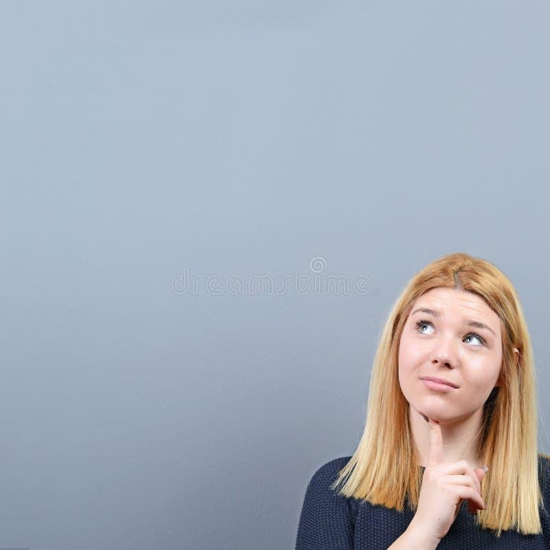 Portret van nadenkende jonge vrouw die lege ruimte boven haar hoofd tegen grijze achtergrond bekijken royalty-vrije stock foto