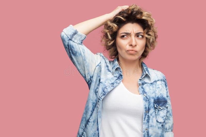 Portret van nadenkende verwarde jonge vrouw met krullend kapsel in toevallig blauw overhemd die krassend haar hoofd en het denken stock fotografie