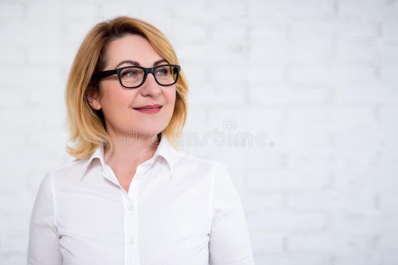 Portret van nadenkende vrolijke rijpe bedrijfsvrouw in oogglazen die over witte muur stellen stock afbeeldingen