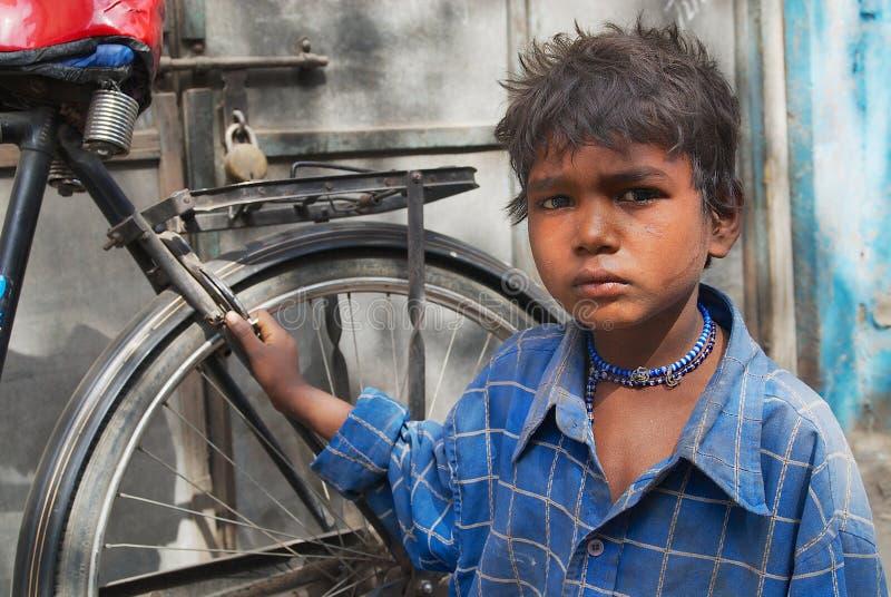 Portret van niet geïdentificeerde jongen met een fiets bij de straat van Jodhpur, India stock foto