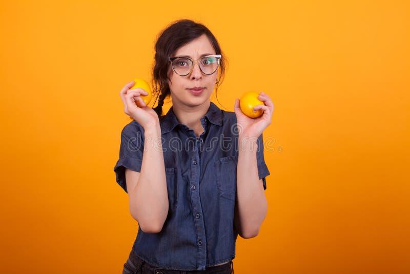 Portret van nieuwsgierige jonge vrouw met twee sinaasappelen in haar handen over gele achtergrond in studio stock foto's