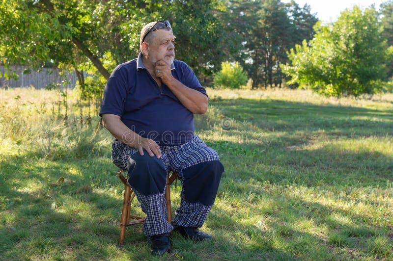 Portret van Oekraïense nadenkende hogere mensenzitting op een kruk in de zomertuin royalty-vrije stock afbeelding