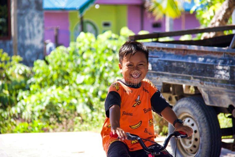 Portret van onbekende het glimlachen Aziatische kindzitting op een fiets royalty-vrije stock foto