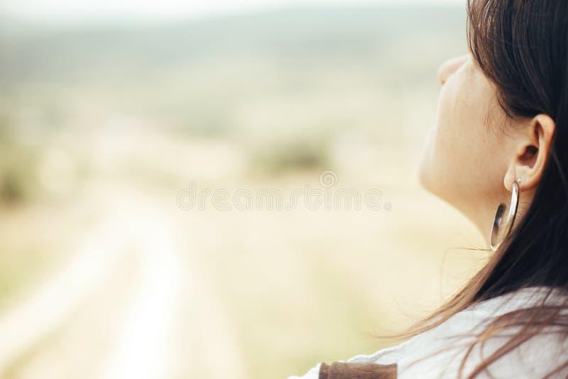 Portret van onbezorgd hipstermeisje die hemel bekijken en in zonnige weide in bergen ontspannen Het modieuze vrouw genieten die b stock fotografie