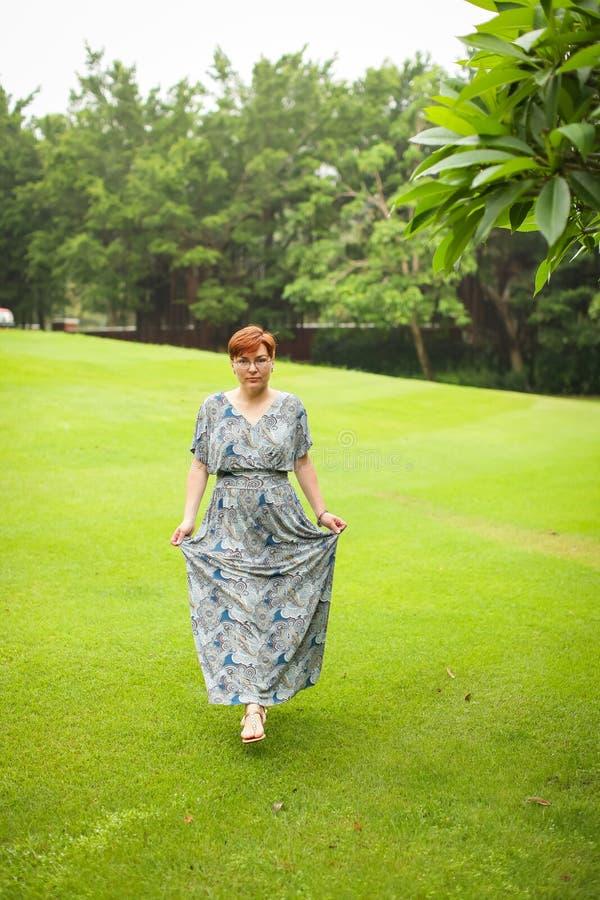 Portret van onbezorgde volwassen Kaukasische roodharigevrouw in kleding het stellen in groen de zomerpark royalty-vrije stock foto
