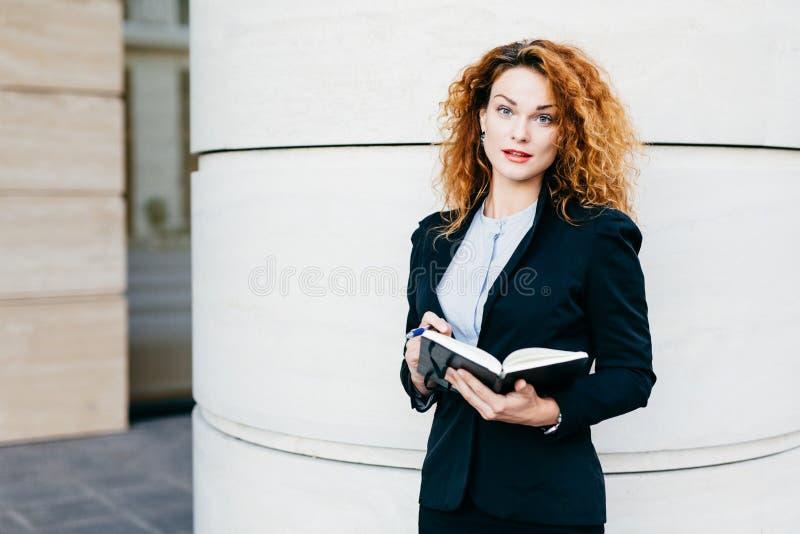 Portret van onderneemster met krullend haar, rode geschilderde lippen, die elegante kleren dragen, die in haar agendaboek schrijv stock afbeeldingen