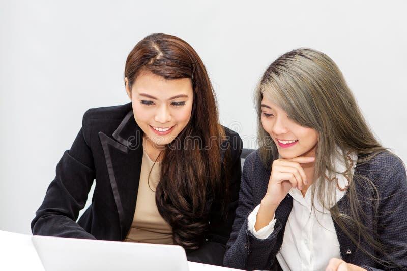Portret van onderneemster twee die laptop in bureau met behulp van Aziatische peo stock foto