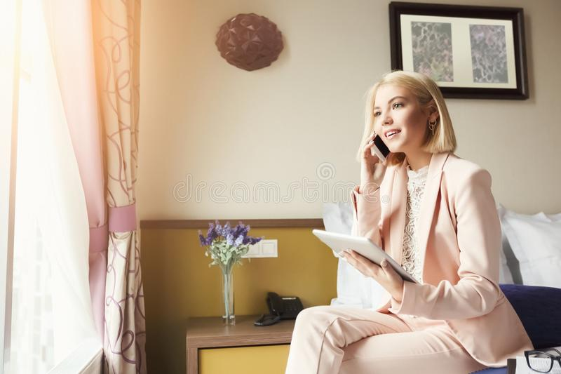 Portret van onderneemsterzitting op bed en het gebruiken van tablet stock afbeelding