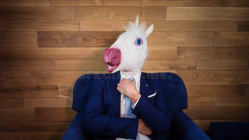 Portret van ongebruikelijk eenhoorn thuis bureau Freaky jonge manager in komisch masker stock afbeeldingen