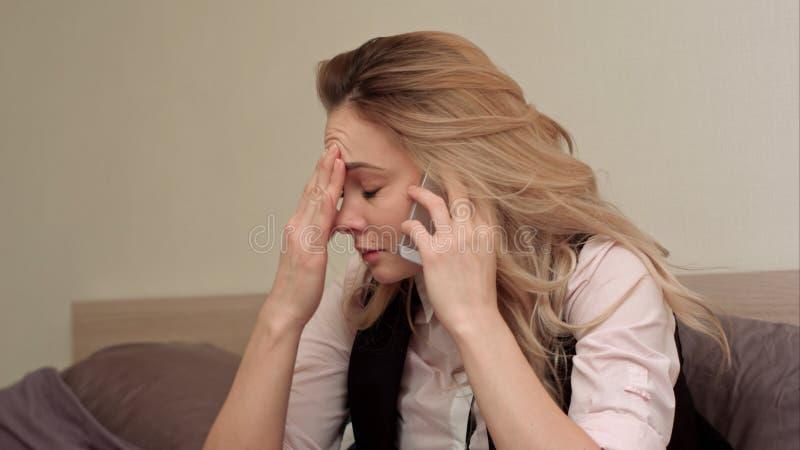 Portret van ongelukkige jonge vrouw die geërgerd telefoongesprek thuis maken stock foto's