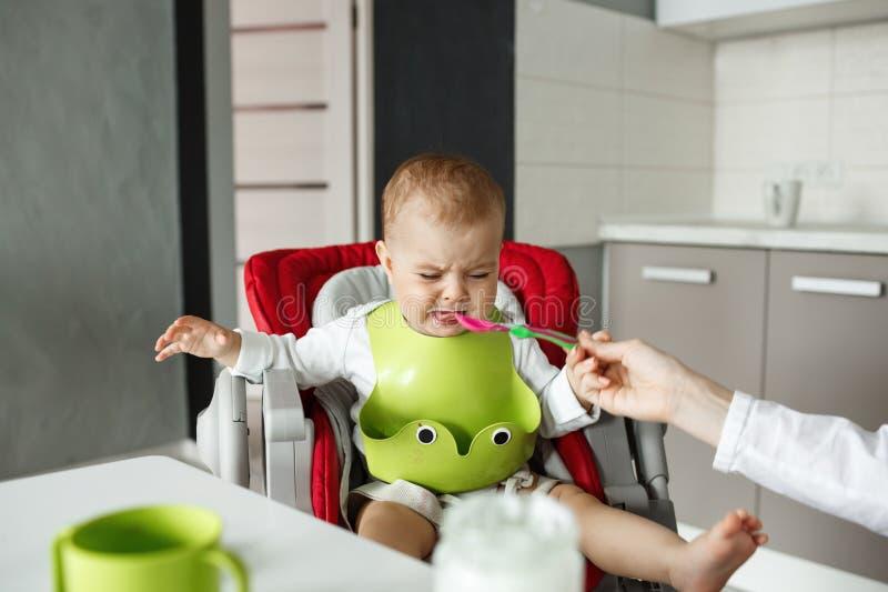 Portret van ongelukkige pasgeboren zoon in groene slab die en van de lepel weigeren te eten terwijl moeder die geduldig proberen  stock afbeeldingen