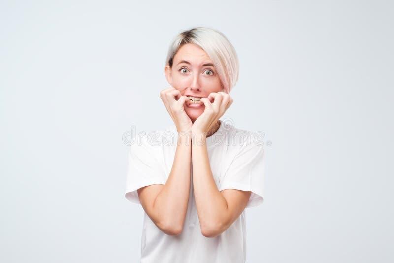 Portret van ongerust gemaakte doen schrikken vrouw die met geverft kort haar camera, studioschot bekijken stock fotografie