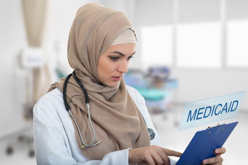 Portret van ongerust gemaakte moslim vrouwelijke Medische artsenholding paperclip in het ziekenhuis royalty-vrije stock afbeeldingen
