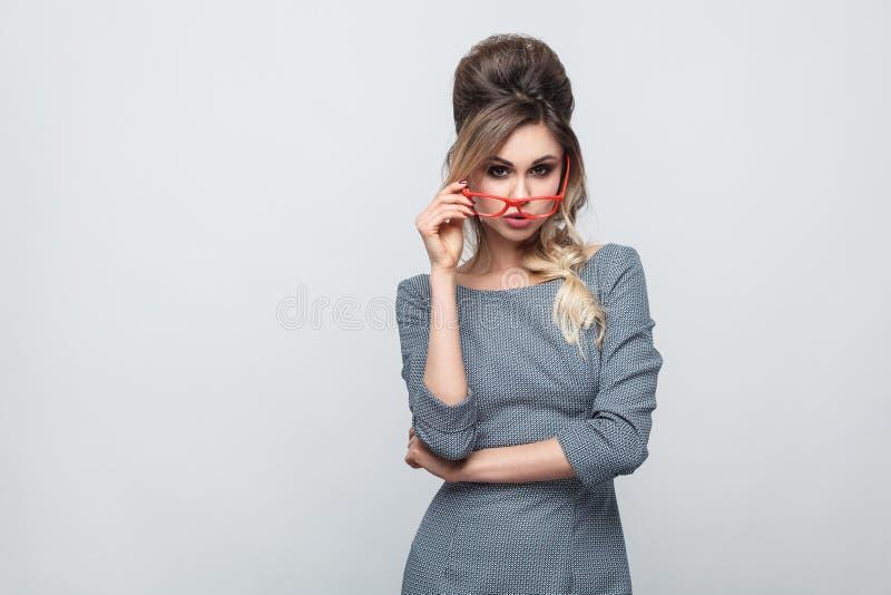 Portret van ontevreden mooi jong meisje in grijze kleding met vlecht op hoofd status, het houden van rode glazen en het bekijken  royalty-vrije stock afbeelding