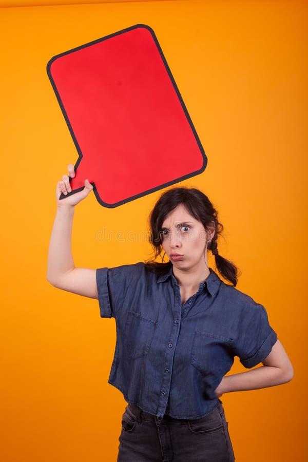 Portret van ontevredenheids jonge vrouw die een lege gedachte bel in studio over gele achtergrond houden royalty-vrije stock fotografie