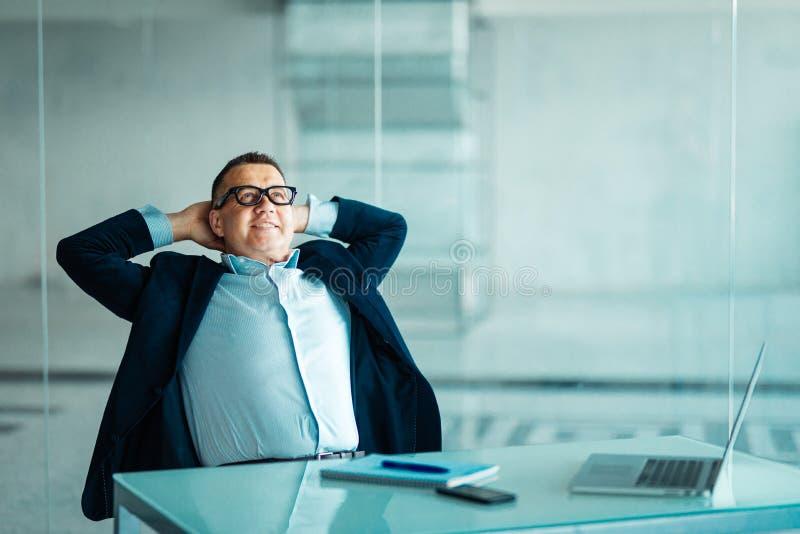 Portret van ontspannen hogere managerzitting op kantoor en terug het leunen royalty-vrije stock fotografie