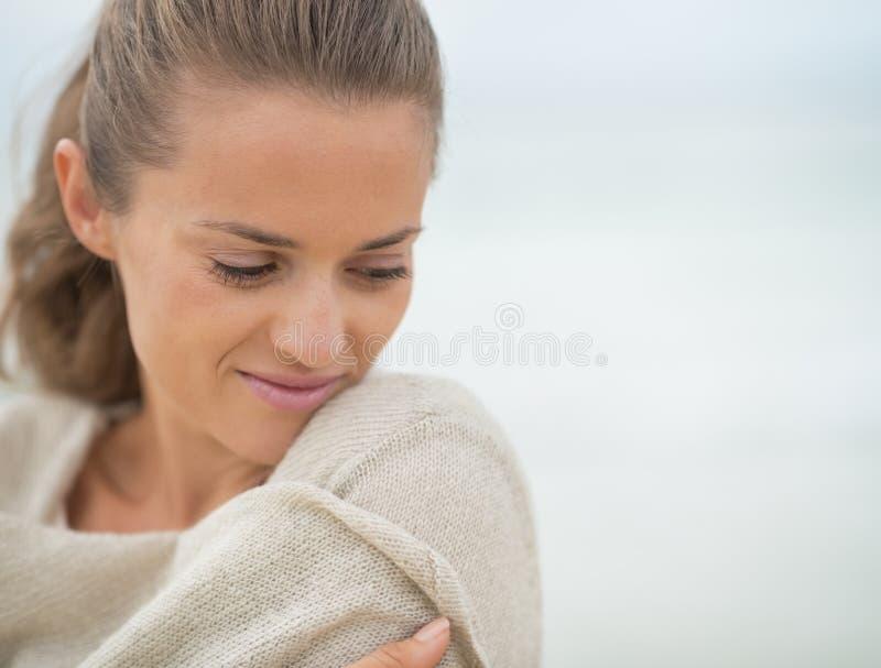 Portret van ontspannen jonge vrouw op koud strand royalty-vrije stock afbeelding