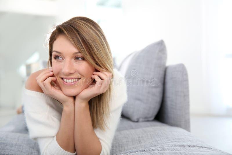 Portret van ontspannen mooie vrouw op bank royalty-vrije stock afbeeldingen