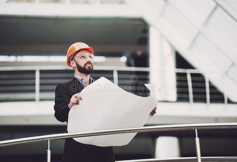 Portret van ontwikkelaar in bouwvakker die dichtbij bouwen stock afbeeldingen