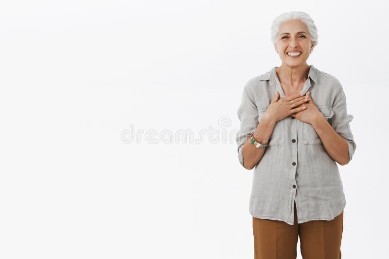 Portret van opgetogen charmant oud wijfje met de grijze gekamde palmen van de haarholding op borst met tevreden en dankbare gliml stock foto