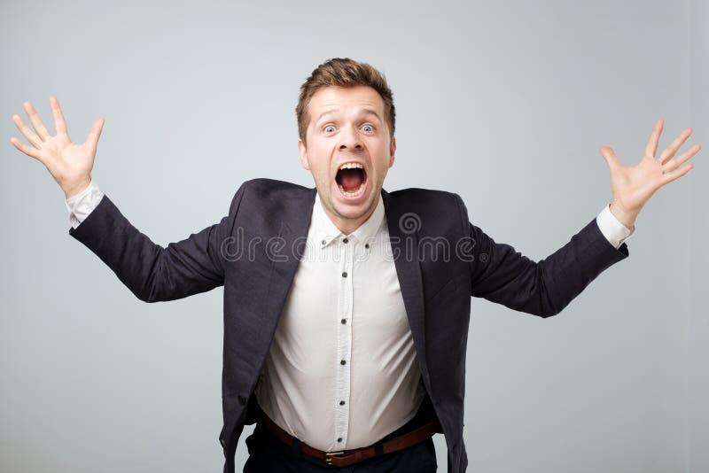 Portret van opgewekt jong mannetje die in kostuum in schok en verbazingholdingshanden omhoog gillen stock foto's