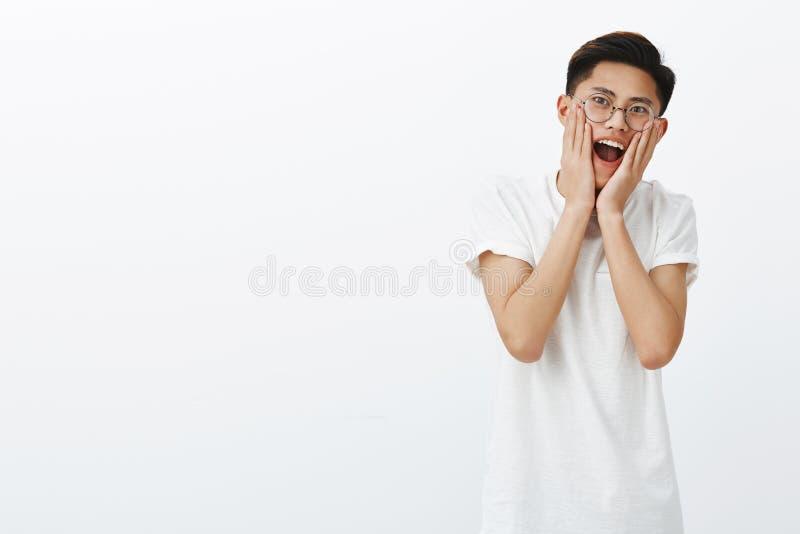 Portret van opgewekt verrast en charismatisch jong aantrekkelijk Aziatisch mannelijk model met modieus kapsel in ronde glazen stock afbeelding