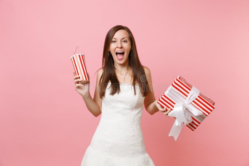 Portret van opgewekte gelukkige bruidvrouw die in huwelijkskleding rode doos met gift, huidige en plactic kop met kola houden of stock fotografie