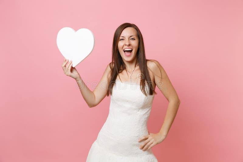 Portret van opgewekte gelukkige bruidvrouw in elegant wit bevindend de holdings wit hart van de huwelijkskleding met exemplaarrui stock foto's
