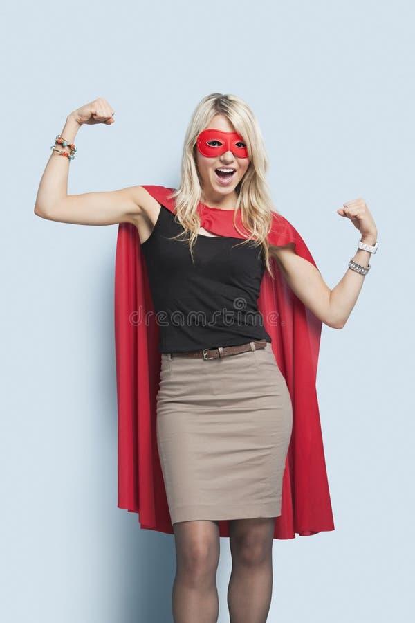 Portret van opgewekte jonge blonde vrouw in de verbuigingswapens van het superherokostuum over lichtblauwe achtergrond stock afbeeldingen