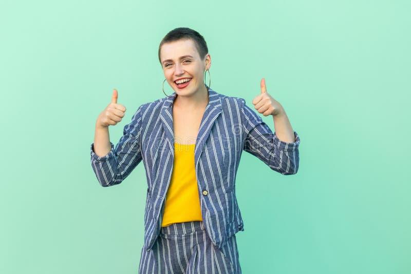 Portret van opgewekte knappe mooie korte haar jonge modieuze vrouw in toevallig gestreept kostuum die, duimen, toothy glimlach op stock fotografie