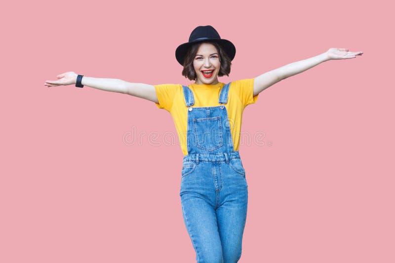 Portret van opgewekte mooie jonge vrouw in gele t-shirt, blauwe denimoverall die, make-up, zwarte hoed zich met opgeheven wapens  stock foto