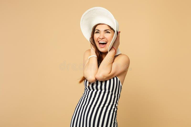 Portret van opgewekte vrolijke vrouw die in die zwart-witte gestreepte kleding, hoed hand op hoofd zetten op pastelkleurbeige wor royalty-vrije stock foto's
