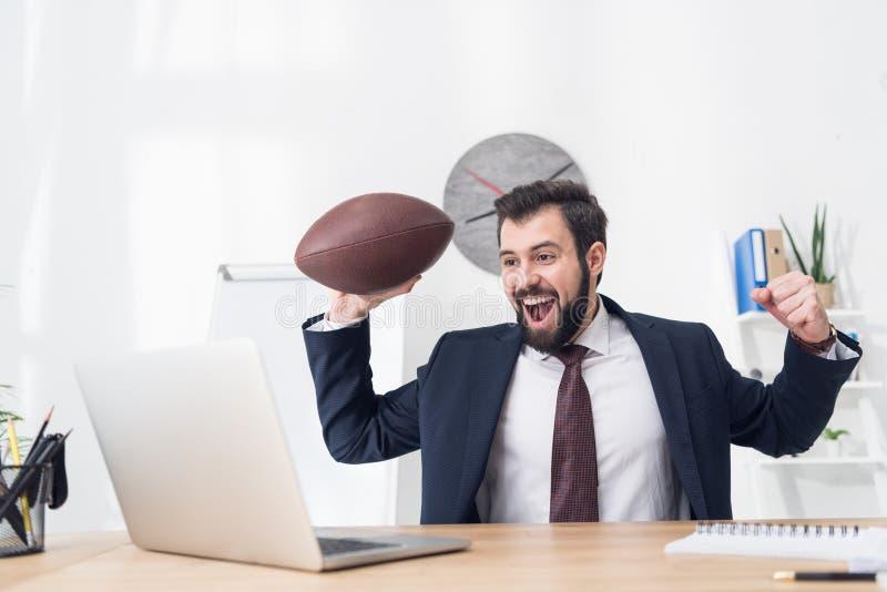 portret van opgewekte zakenman met rugbybal bij werkplaats met laptop royalty-vrije stock foto's