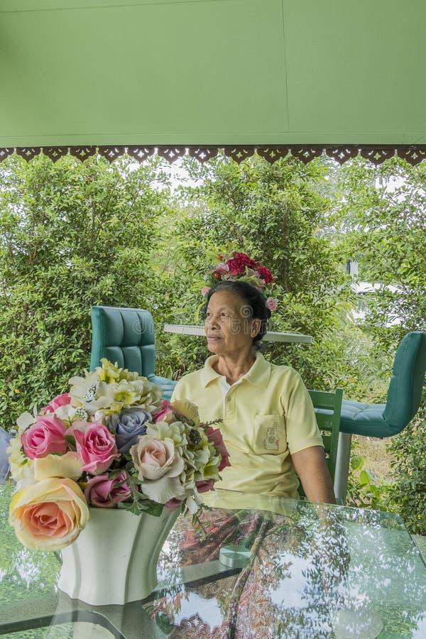 Portret van oude Aziatische Thaise vrouwenzitting op stoel royalty-vrije stock afbeelding