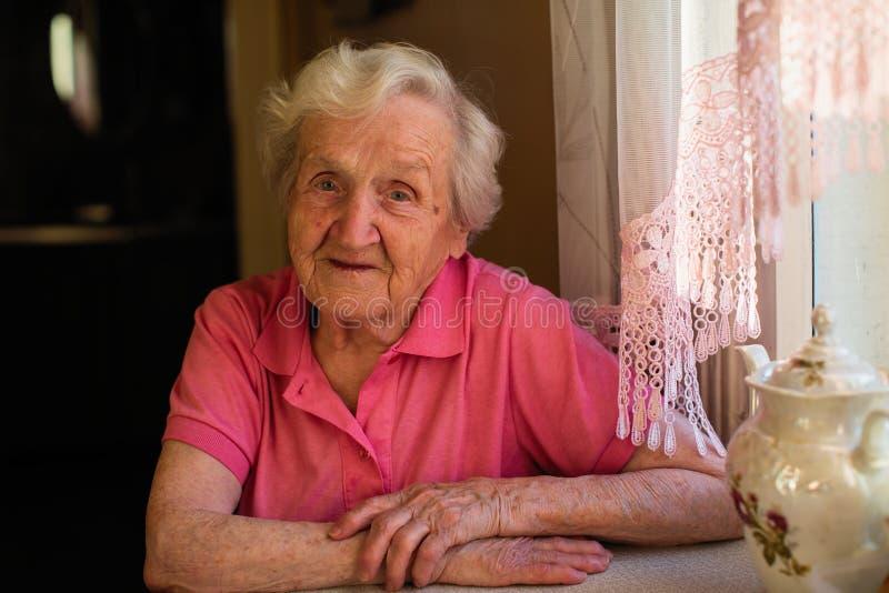 Portret van oude gelukkige vrouwenzitting bij de lijst stock afbeelding