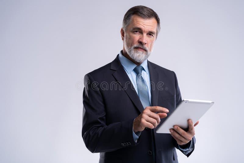 Portret van oude zakenman die kostuum en band dragen Zakenman in jaren die zich op witte achtergrond bevinden Chef- gebruikende t royalty-vrije stock fotografie