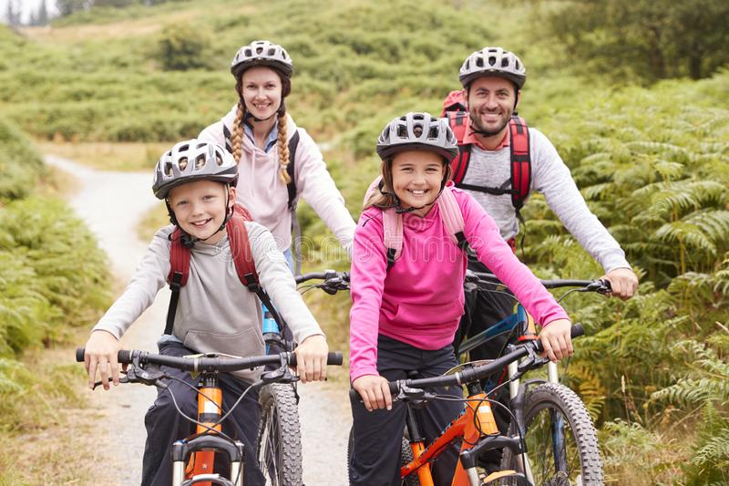 Portret van ouders en kinderen die op bergfietsen in een steeg van het land tijdens een familie het kamperen reis, vooraanzicht z royalty-vrije stock afbeelding