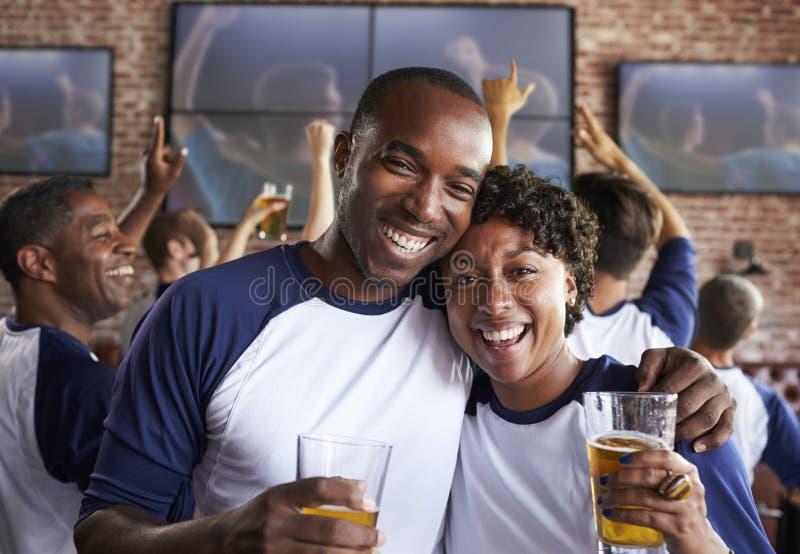 Portret van Paar het Letten op Spel in Sportenbar op de Schermen stock fotografie