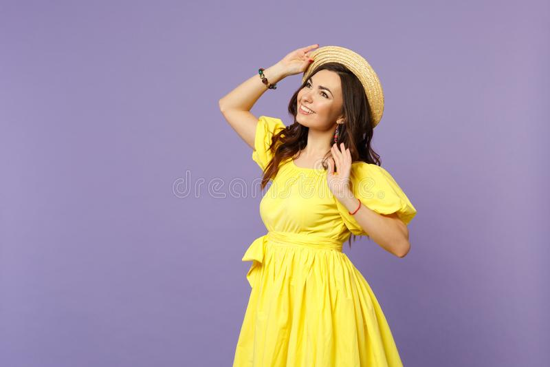 Portret van peinzende glimlachende jonge vrouw in gele kleding die hand op de zomerhoed houden die omhoog kijken die op pastelkle royalty-vrije stock foto's