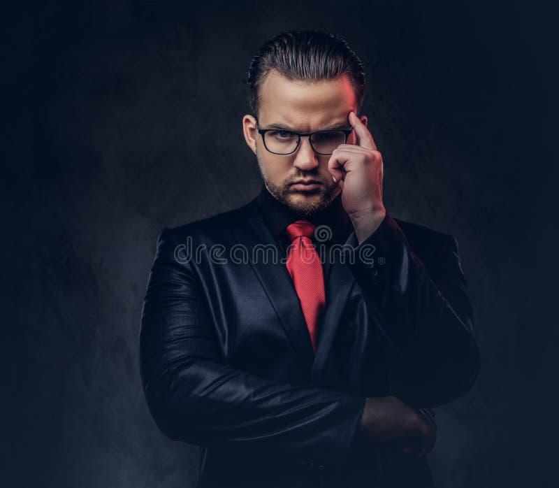 Portret van peinzende modieuze mannelijk in een zwart kostuum en een rode band stock foto