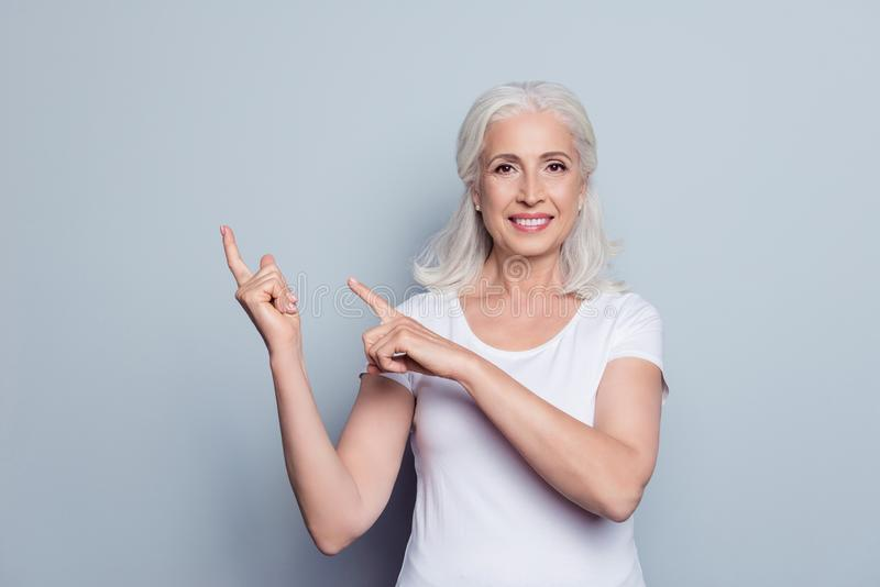 Portret van perfecte, aardige, oude, glimlachende vrouw in t-shirt demonst stock foto's
