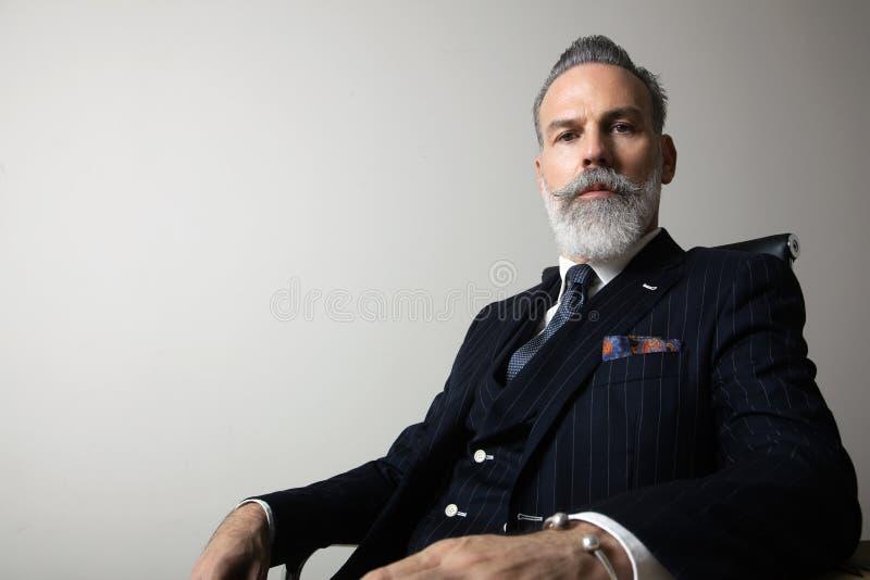 Portret van positieve gebaarde heer die in kostuum over lege grijze achtergrond dragen De ruimte van het exemplaardeeg Het schot  stock foto's