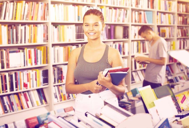 Portret van positieve meisjestiener die nieuwe boeken houden stock foto